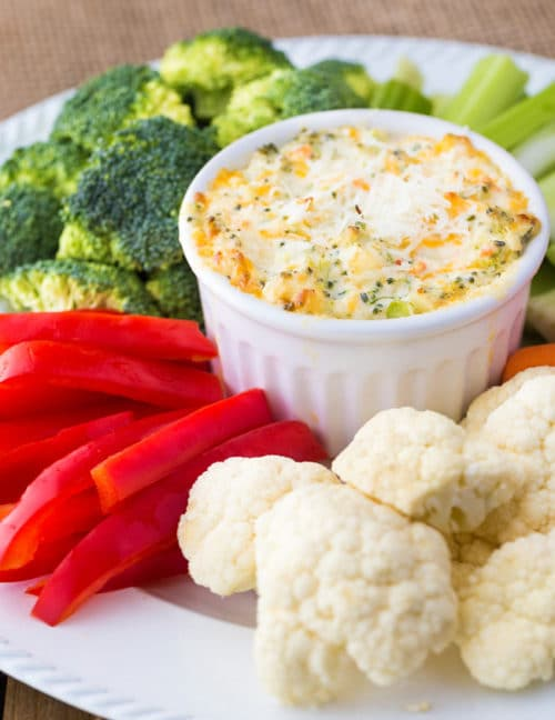 Hot broccoli dip on a serving platter surrounded by broccoli, red pepper, celery, and cauliflower.
