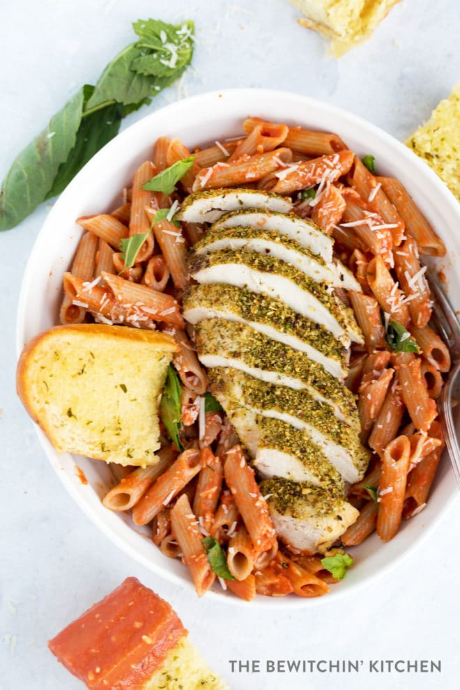 Sliced chicken breast crusted in herbs over penne pasta and sauce.