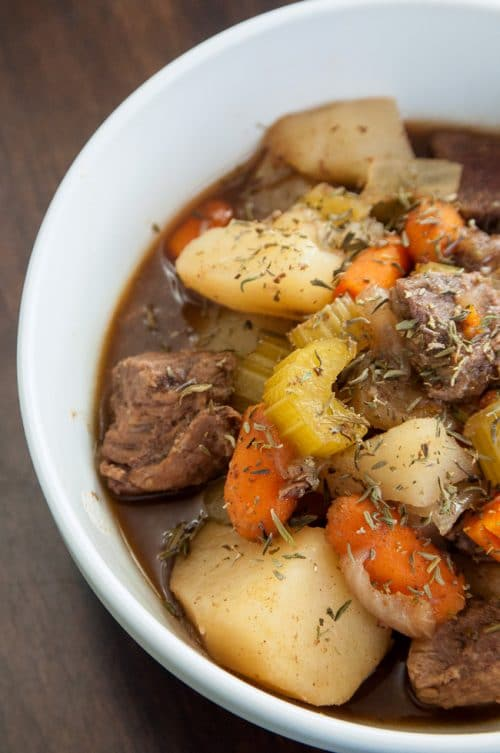 A white bowl full of beef stew with cooked celery, carrots, and potatoes showing.