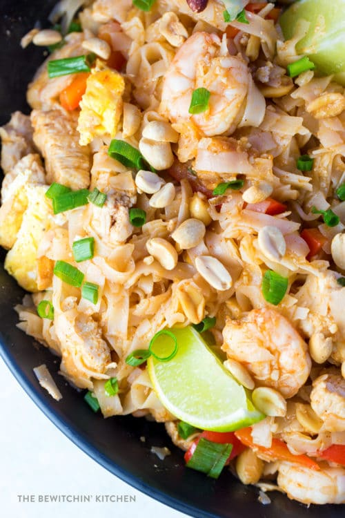 Pad Thai with limes, green onions, peanuts, eggs, and chicken breasts.