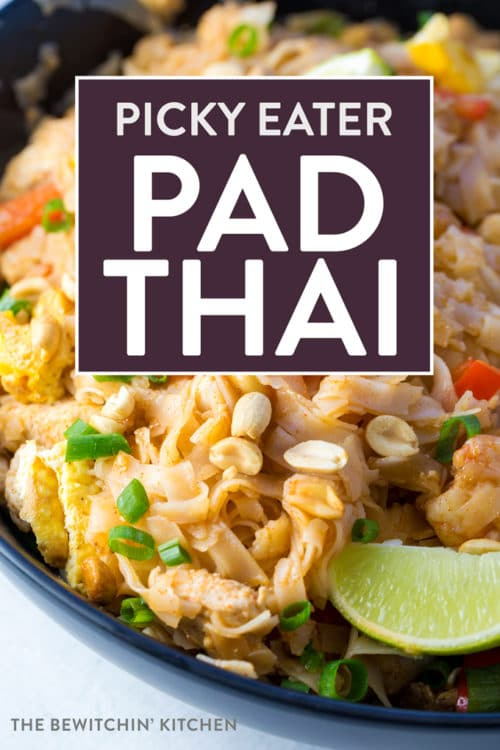 Pad thai with limes and peanuts in a black bowl.