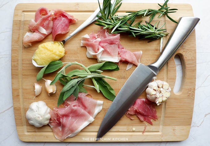 prosciutto, rosemary, and sage on a cutting board