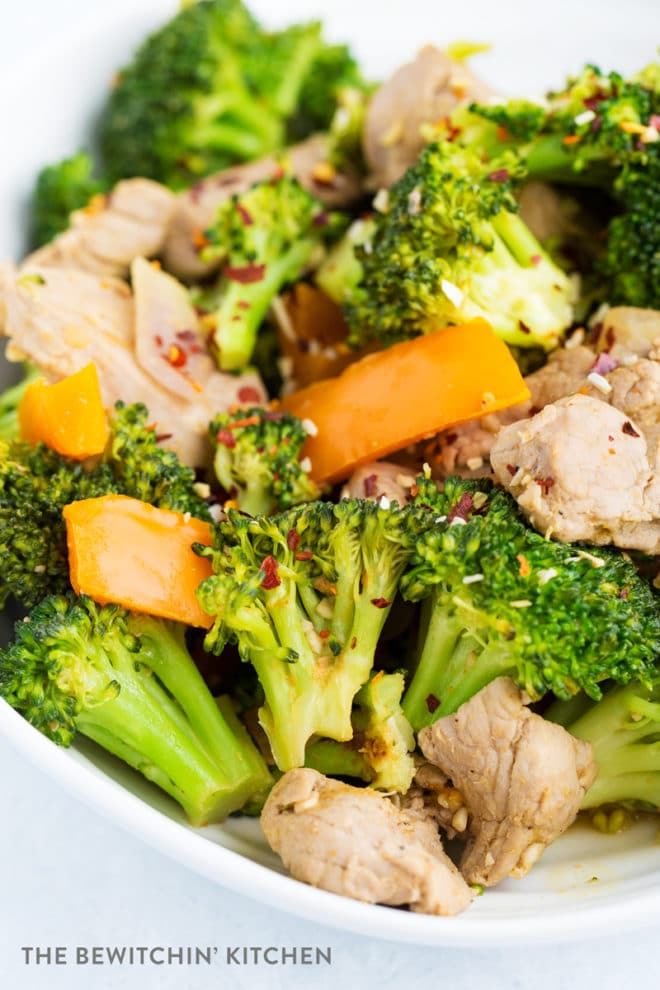 Overhead view of cooked broccoli, orange pepper, red onion, and pork. Stir fried and served on a white plate.