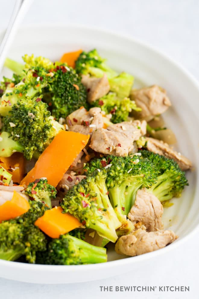 Broccoli, orange bell pepper, and pork tenderloin cooked in a pretty white bowl.