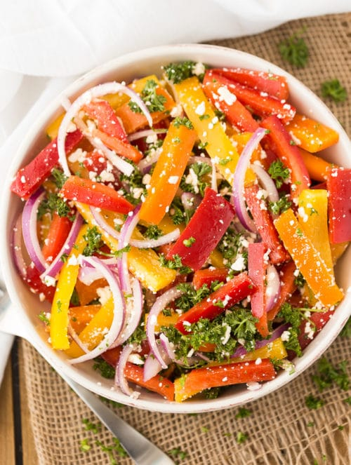 An overhead look at a marinated bell pepper salad with red onions and feta cheese.