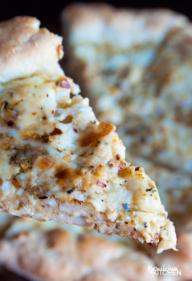 A slice of pizza made with italian salad dressing, parmesan, and cheese lifted towards the camera.