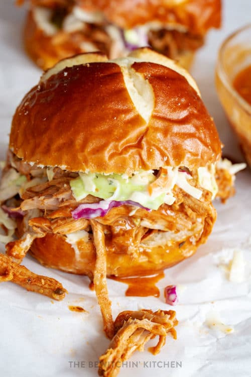 slow cooker pulled pork in a pretzel bun with coleslaw and dripping spicy bbq sauce