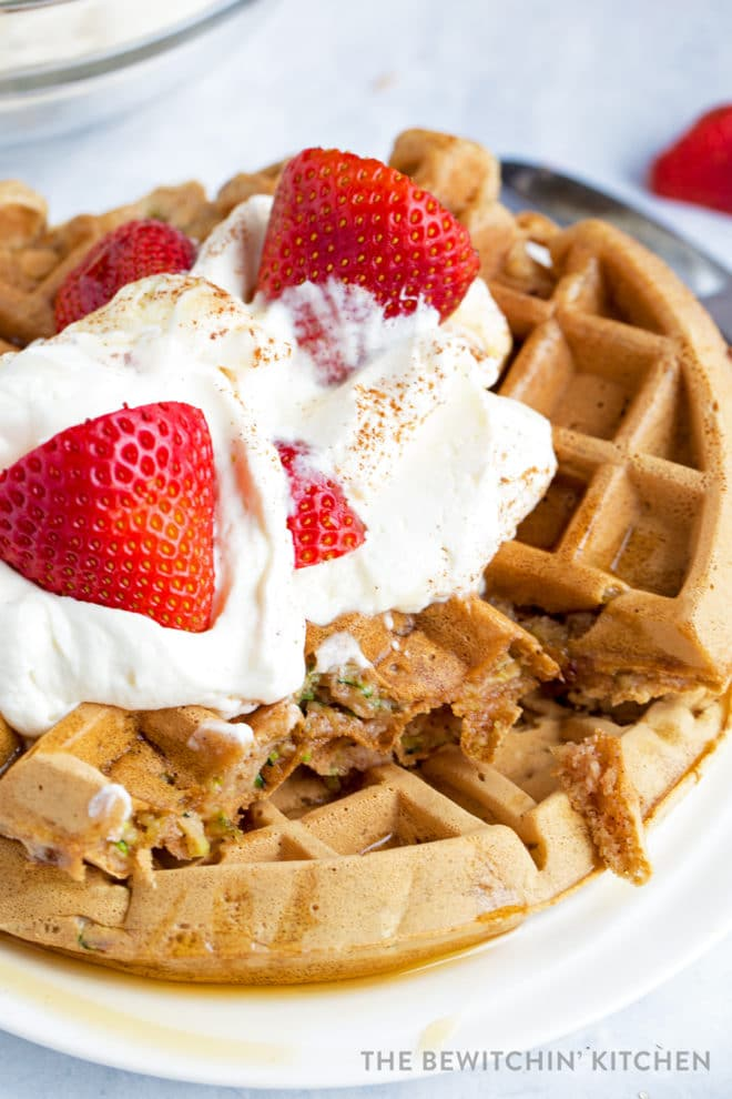 Waffles topped with whipped cream, maple syrup and strawberries cut with zucchini showing.