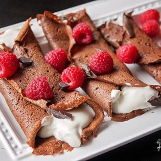 This recipe for healthy chocolate crepes is gluten free and grain free. It's filled with a protein packed greek yogurt and whipped cream mixture and topped with raspberries and dark chocolate. Add this to your healthy breakfast recipes and healthy dessert recipe board!