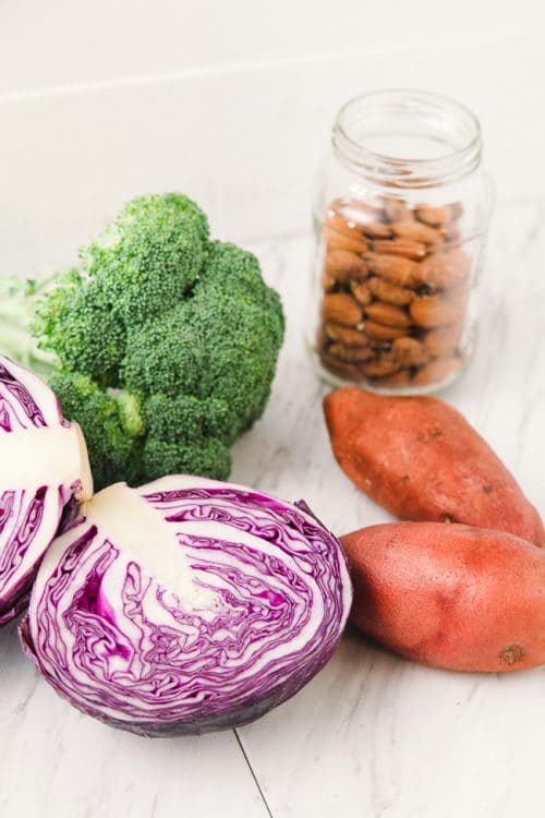 This paleo winter bowl recipe has roasted sweet potato, broccoli, finely shredded red cabbage, pulled together with a creamy vegan almond and honey dressing. Serve as a side dish or add some chicken or tofu for a healthy lunch or dinner.