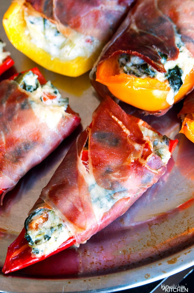 Spinach artichoke stuffed peppers wrapped in prosciutto. Add this to your appetizer recipes. Spinach dip, bell peppers, prosciutto - it sounds like heaven. It has a little kick from jalapenos too. The perfect party food recipe. | thebewitchinkitchen.com