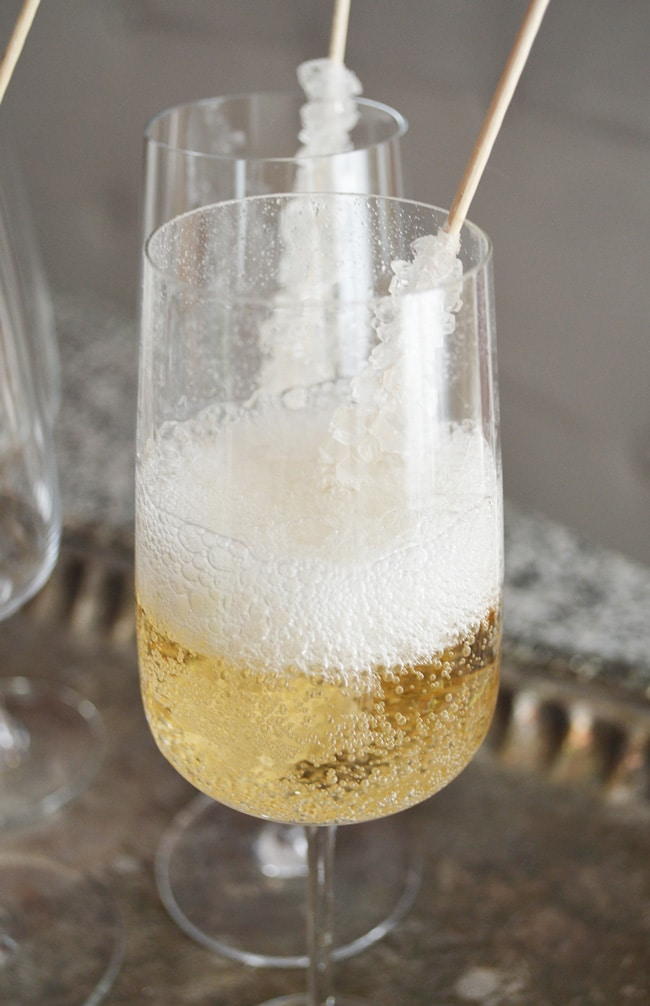 This champagne on the rocks idea is an elegant way to glam up your party (or Friday night). Perfect New Years Eve Party Idea. It's so easy too: sparkling wine and rock candy! An easy and low cost way to add class to your party.