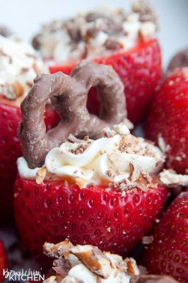 Cheesecake Stuffed Strawberries. This easy, no bake dessert recipe is a party favorite. Cream cheese, sugar and vanilla, topped with crunchy milk chocolate covered pretzels makes this bite sized treat sweet, salty and crunchy. Add this to your popular desserts board.