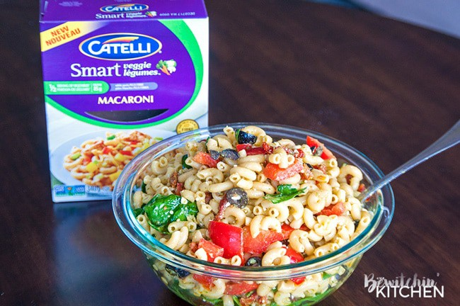 Pesto Pasta Salad - this tangy twist on a macaroni salad is my new favorite summer salad recipe. Sundried tomatoes, smart veggie pasta, spinach, feta cheese, red pepper, and olives tossed in a homemade honey pesto vinaigrette. Also makes a delicious and nutritious addition to a school lunch.