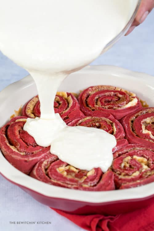 Delicious cream cheese glaze poured over red velvet cinnamon rolls.