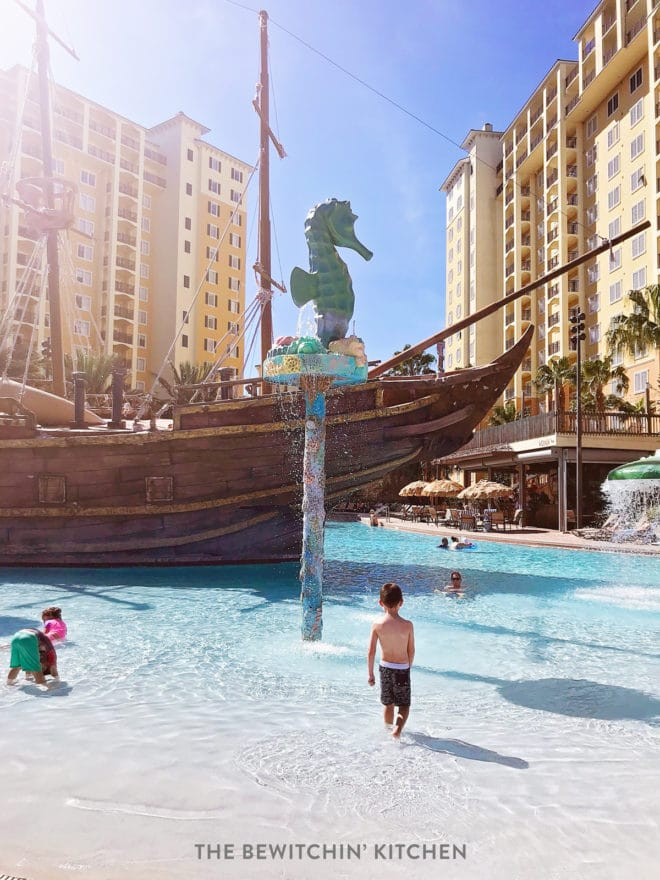 Child in the shallow end of the pool with a pirate ship behind him at Lake Buena Vista Resort in Orlando.