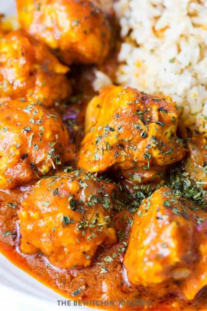 Four chicken meatballs beside a bed of rice with a paleo butter chicken sauce poured over.