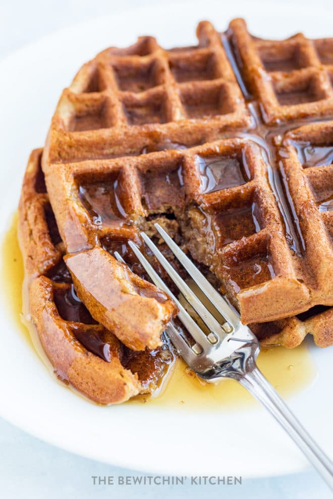 A fork cutting into allergy free waffles with maple syrup.