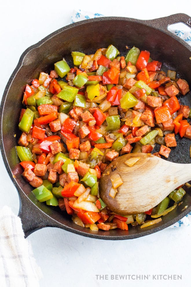Chopped chorizo, onions, and bell peppers sauteing in a cast iron pan