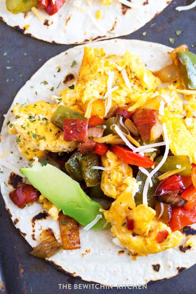 Close up of breakfast tacos with eggs, chorizo, peppers, onions, and avocado