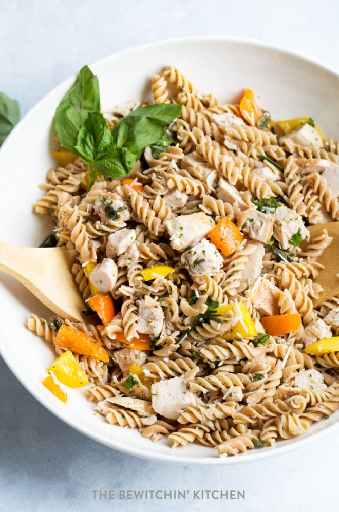 Chicken pasta salad with bell peppers, parmesan cheese, and basil in a bowl.