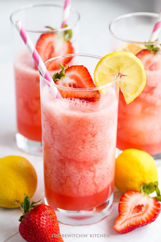 Healthy strawberry lemonade made in a Vitamix with strawberries and lemons beside the glass.