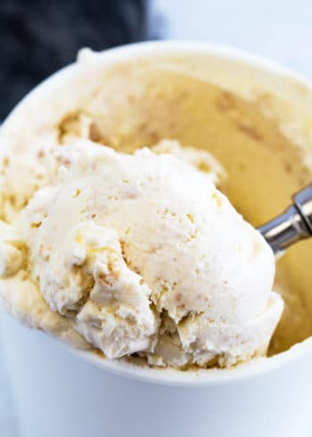No churn key lime pie ice cream being scooped out of a reusable ice cream container.