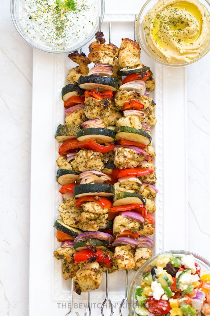 Chicken veggie kebabs on a white platter with hummus, tzatziki, and greek salad.