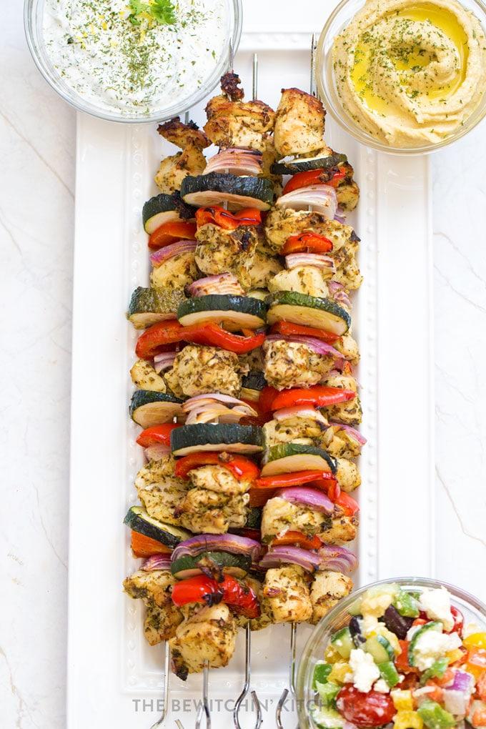 Chicken veggie kebabs on a white platter with hummus, tzatziki, and greek salad.