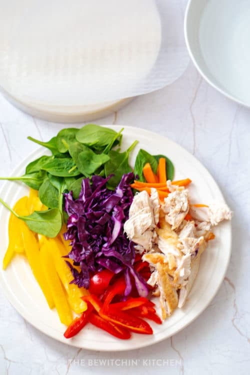 Colorful vegetables with chicken on a spring roll wrapper.