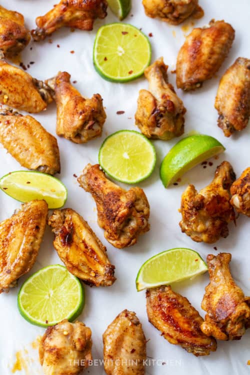 overhead shot of chili rubbed chicken wings with sliced limes on a white background.