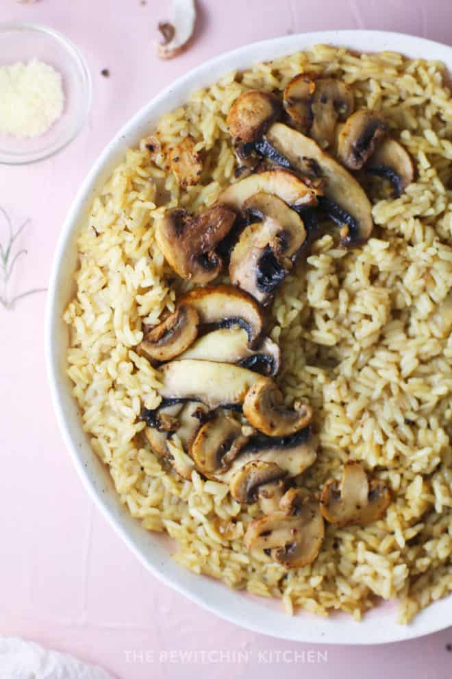 Risotto in a white dish with sliced mushrooms on top