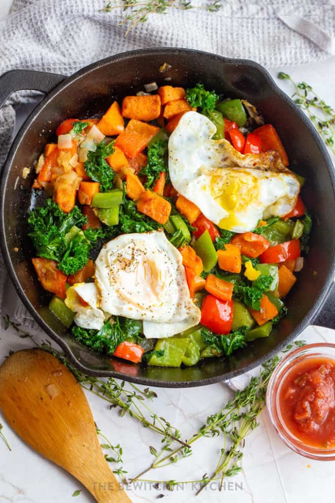 fried eggs over easy in a cast iron skillet surrounded with colorful vegetables