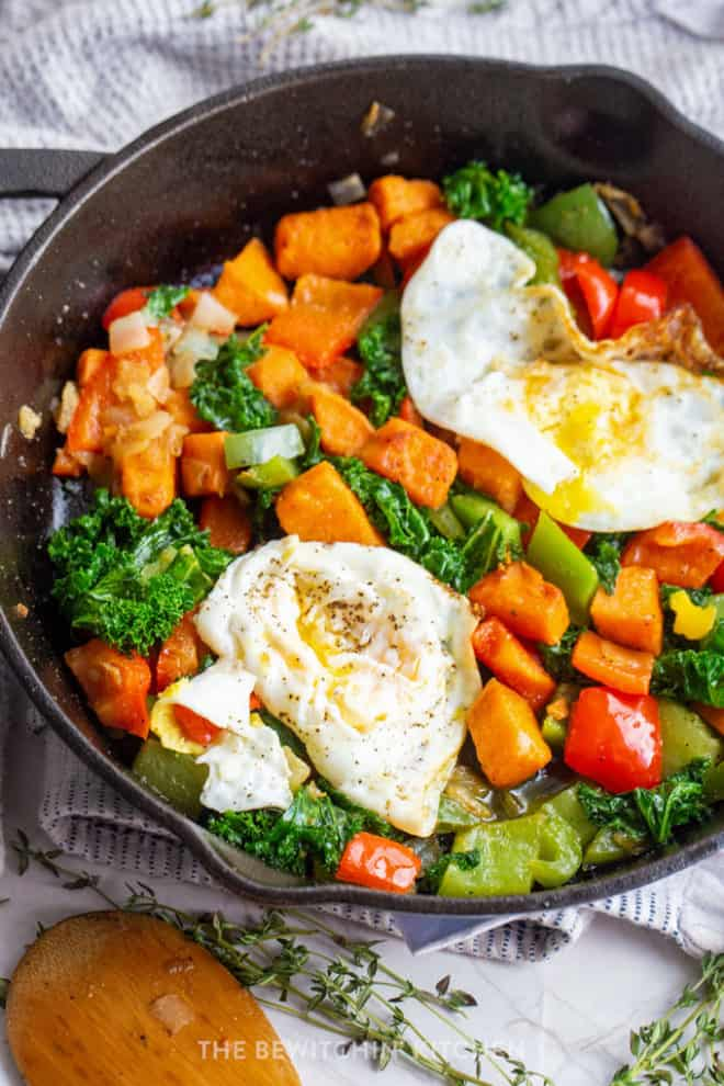 close up of egg cooked over medium in a cast iron skillet with sweet potatoes, kale, and peppers