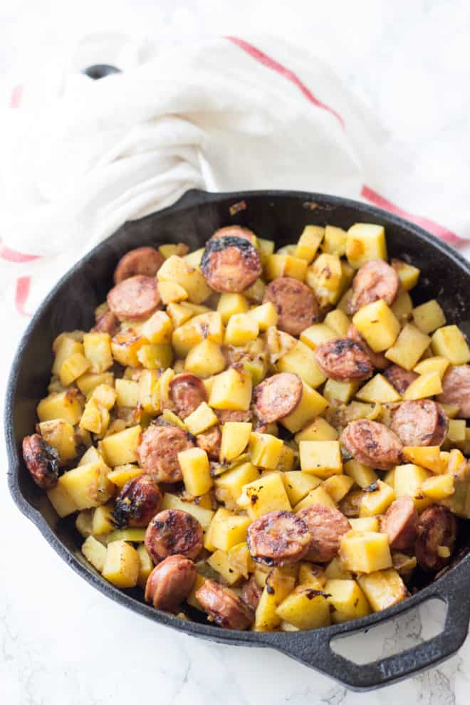 cooked chicken apple sausage with potatoes and apples in a cast iron skillet