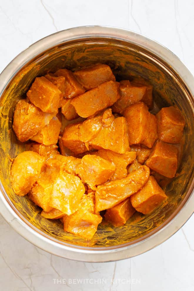 cubed chicken in a curry marinade