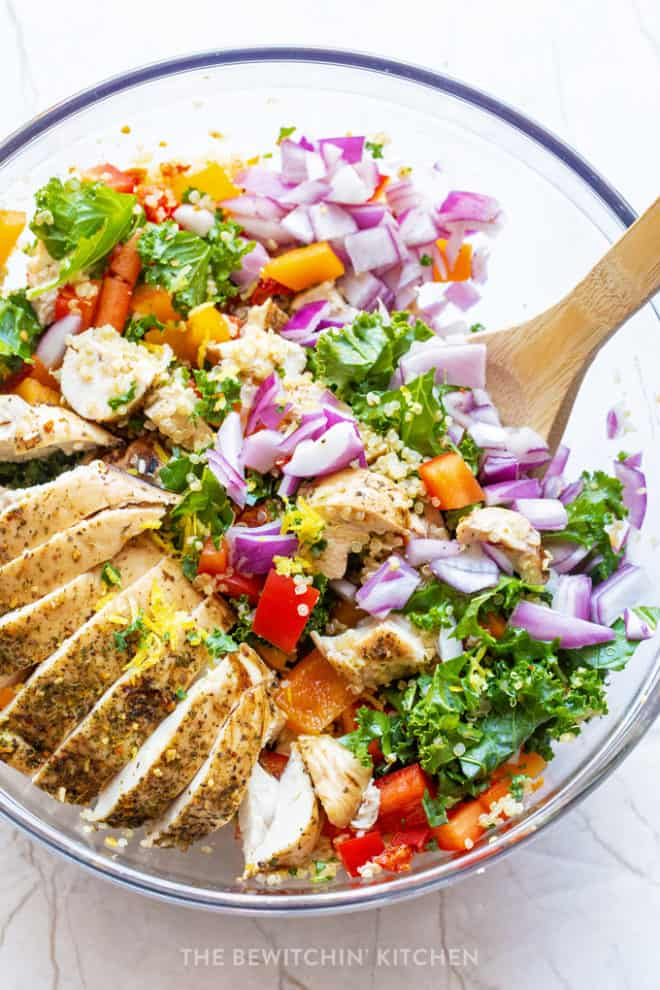 healthy chicken summer salad with red onions, kale, quinoa, and sundried tomatoes