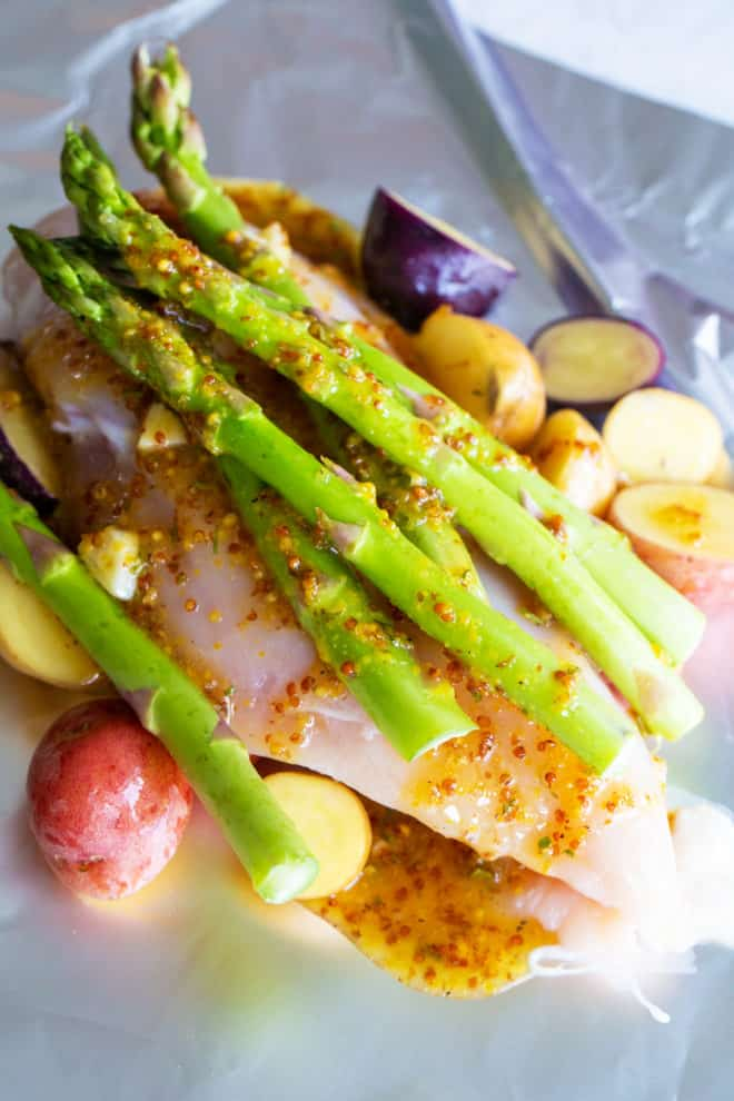 asparagus with chicken, honey mustard, chicken and potatoes on top of foil
